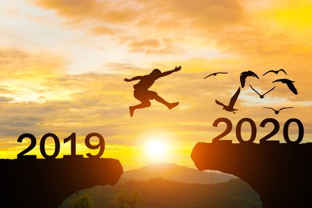 Happy New Year 2020 Men jump over silhouette mountains sun