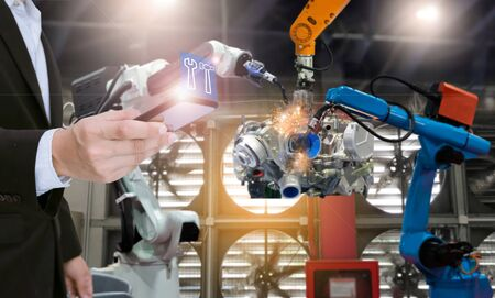System engineer with smartphone control automation robot arms the production of factory parts engine manufacturing industry robots and mechanical arm Imagens