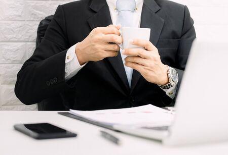 Coffee break businessman executive working relax on laptop at his desk. Foto de archivo