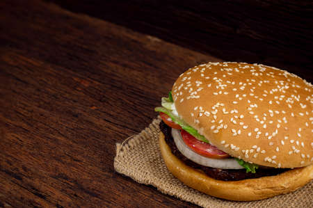 Hamburger meat and vegetables on wooden background