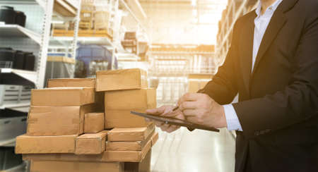 businessman export or manager concept with tablet clipboard checking goods at warehouse
