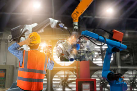 Engineering controlling machinery and industrial robots of things technology man using for control Foto de archivo
