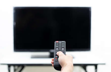 Hand holding the remote to turn on the TV