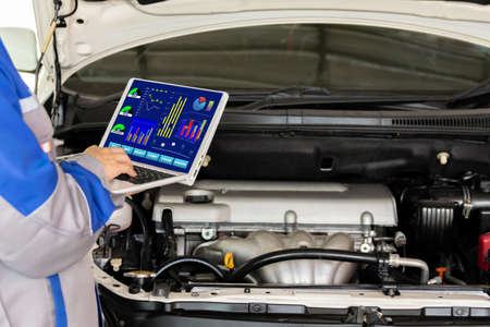 The mechanic adds distilled water and check the car battery