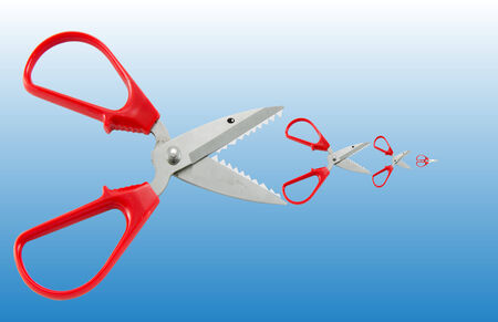 Scissors concept as big fish eat small fish photo