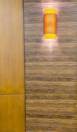 topical: Topical orange lamp on wood wall