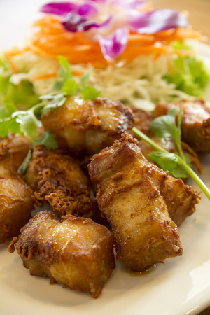 Deep-fried pork belly, that marinate with fish sauce and spices on white ceramic plate, Thai recipe.