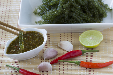 Sea grapes or green caviar and spicy sauce on a white dish the wooden dish made of Japanese style bamboo, Thailand.