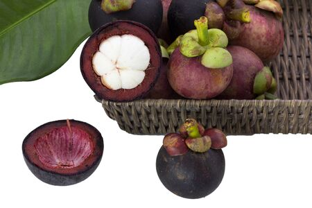 Ripe mangosteens (Garcinia mangostana) with green leaves in a basket on the white background, mangosteen queen. Imagens