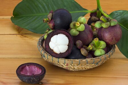 Ripe mangosteens (Garcinia mangostana) with green leaves in a basket on the wooden table, mangosteen queen. Imagens