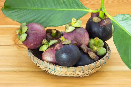 Ripe mangosteens (Garcinia mangostana) with green leaves in a basket on the wooden table, mangosteen queen. Stock Photo