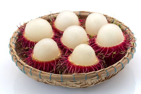 Fresh Rambutan with green leaves in a basket isolated on white background, Thailand.
