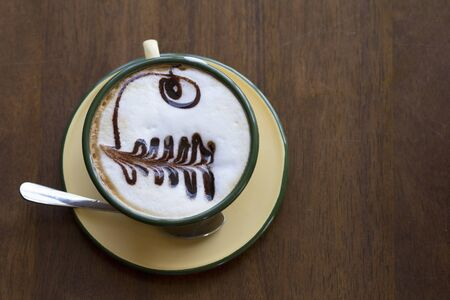 Cup of coffee is beautifully decorated, Coffee cup and coffee beans on a wooden table, Top view.