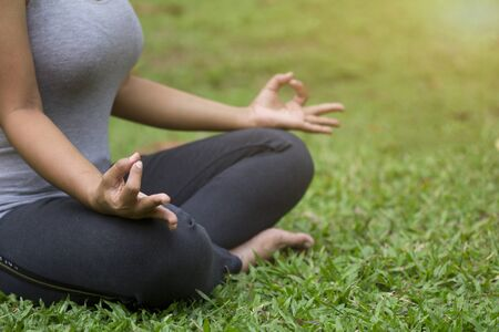 Woman do yoga outdoor, Yoga in the park, Close up hands, Meditation, Concept of healthy lifestyle and relaxation.