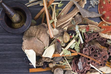 Chinese herb selection used in traditional alternative herbal medicine with mortar and pestle on wood background. Natural herbs medicine, and herbal medicinal root. Alternative Medicine Herbal