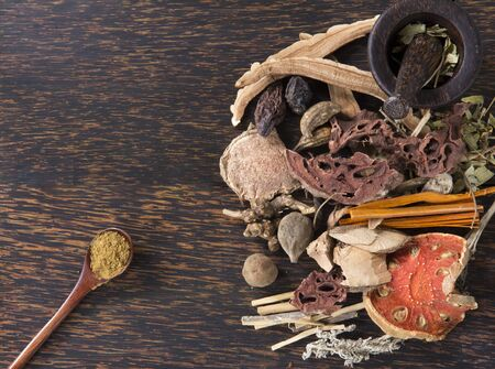 Chinese herb selection used in traditional alternative and Herb powder in a wooden spoon with mortar on wood background. Natural herbs medicine, and herbal medicinal root. Alternative Medicine Herbal