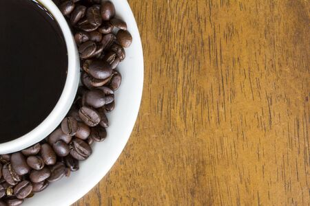 Close up of Hot coffee cup and coffee beans on wooden table background near the window with a light shade on the tabletop at cafe, white ceramic cups, espresso, Top view with copy space for your text Stok Fotoğraf