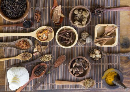 Chinese herb selection used in traditional alternative herbal medicine with mortar and pestle on wood background. Natural herbs medicine and herbal medicinal root. Alternative health care fresh herbal