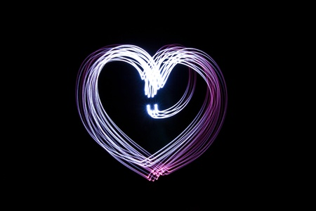 flash light: Heart created by light over black background   Stock Photo