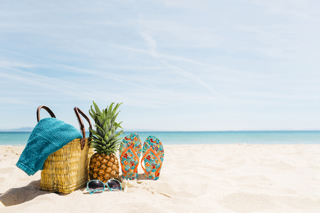 Summer picnic on a sunny beach. Basket, towel, pineapple and sandals on white sands and clear blue ocean. Stock Photo