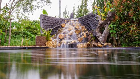 Fish pond with waterfall fountain. Garden waterfall landscaping with fishes, rocks, flowers and plants.