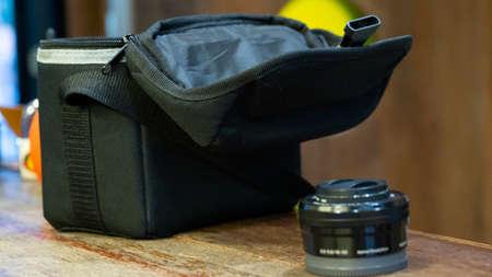 Camera lens beside a camera holder bag