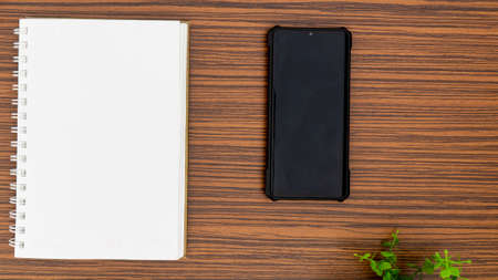 Personal note book and a black mobile phone with a glimpse of green plant on a striped brown office table