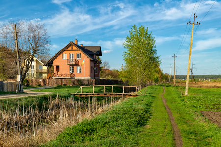 Typical Ukrainian rural landscape in spring. Two-storey house with the Ukrainian flag stands on the banks of a small river with a wooden bridge over it. Stock Photo