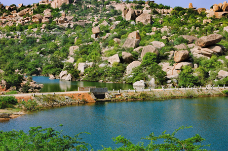 Blue waters of the Tungabhadra River in Hampi, India. River landscape with picturesque rocks on the shore, tropical nature and the road to the ancient ruins across the bridge