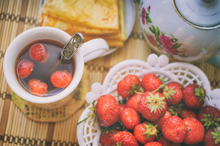 Crepes and Fresh strawberry tea in white cup, teapot, ripe strawberries in a vase and crepes. Breakfast composition for country family in the morning, top view. Image with filter effect instagram