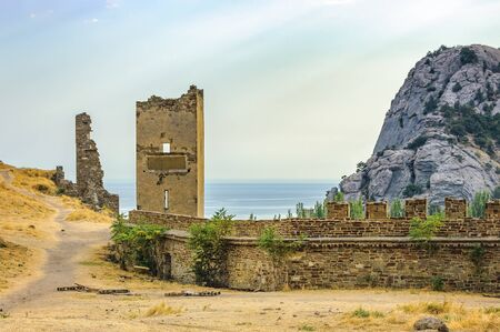 Walls of Genoese fortress in Sudak, Crimea. Scenic views of rocky cliffs near ancient Genoese fortress and modern city in the background Stock Photo