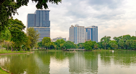 Bangkok, Thailand - December 23, 2015: Business district cityscape with Bangkok skyline, cloudy sky and reflection. Lumphini Park is a popular place for walks and sport activities Editorial