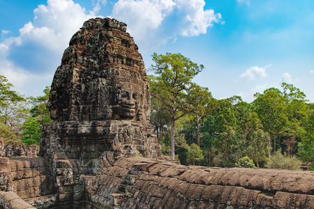 Smiling stone faces of Prasat Bayon, the central temple of Angkor Thom Complex, Siem Reap, Cambodia. Ancient Khmer temple is surrounded by tropical trees, famous Cambodian landmark,