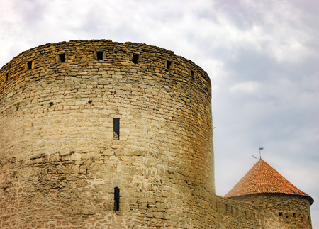 sully: Walls, arched windows and the pointed conical roof of Fortress Akkerman in the morning mist, Bilhorod-Dnistrovskyi, Ukraine. This medieval fortress dates from the 13th century. Stock Photo