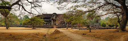 Ancient ruins of temple complex Angkor Wat surrounded by old tropical trees, Siem Reap, Cambodia. Road to the temple in the foreground Stock Photo