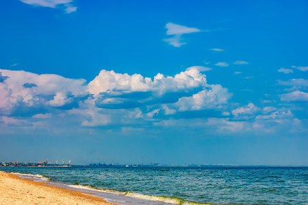 Coastline of the Sea of Azov with sandy beach in a sunny day, Ukraine. Port of Mariupol on the horizon Stock Photo