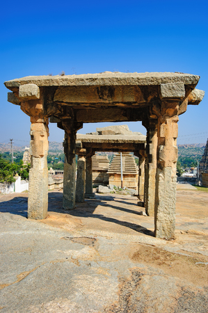 View of ancient ruins on Hemakuta hill in Hampi, Karnataka, India. Landscape with unique mountain formation with amazing stones, tropical nature and temple. Stock Photo