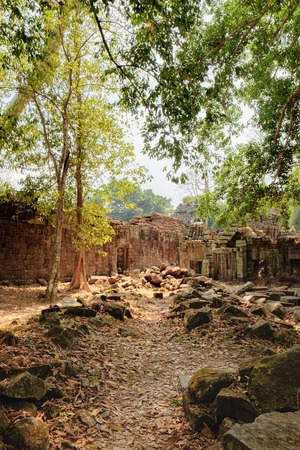 khan: The ancient ruins of the Preah Khan Temple in Siem Reap, Cambodia. A pile of old stones on a tourist road in the foreground. Ancient Khmer architecture, famous Cambodian landmark, World Heritage Stock Photo
