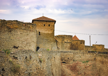 Walls, arched windows and the pointed conical roof of Fortress Akkerman in Bilhorod-Dnistrovskyi, Ukraine. Around the castle is drained the moat, which had previously been water.