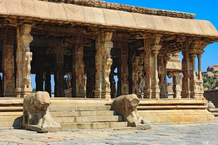 Lions in the foreground guard Bala Krishna Temple at ancient ruins of Hampi, Karnataka, India. Old and famous Indian landmark, World Heritage. Imagens - 83546018