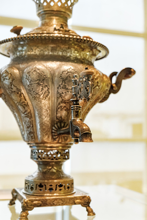 Front view of vintage metal copper tea samovar which was used for a long time. Selective focus Stock Photo