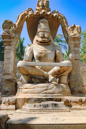 karnataka: The Lakshmi Narasimha statue is the largest monolith statue in Hampi, Karnataka, India. The god is sitting in a cross-legged Yoga position on the coil of a giant seven-headed snake called Sesha. Stock Photo