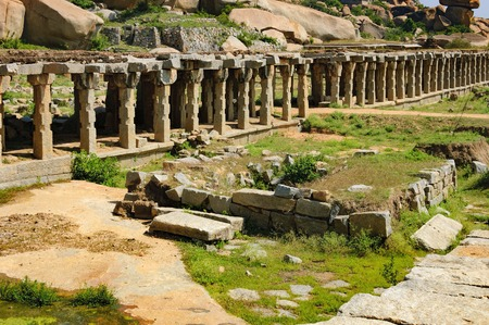 karnataka: View of ancient ruins of Krishna Bazaar in Hampi, Karnataka, India. Landscape with unique mountain formation with tropical nature, hills on the horizon and old hindu temple Stock Photo