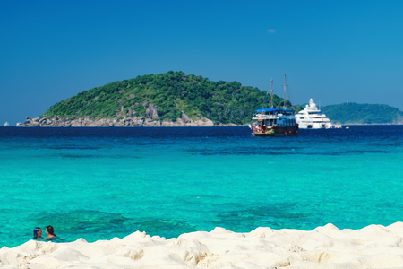 View from the beach to the crystal blue water of the Andaman Sea and Similan Island, Thailand. Loving couple bathes in water, tropical paradise
