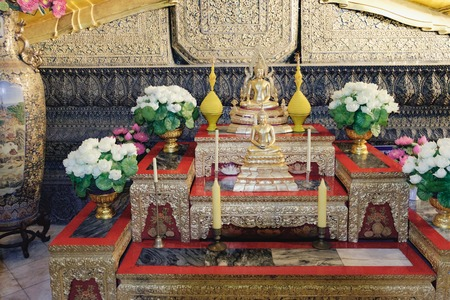 Bangkok, Thailand - December 7, 2015: Golden Buddha statues surrounded by flowers and candles inside the hall of Wat Pho public temple, Bangkok, Thailand.