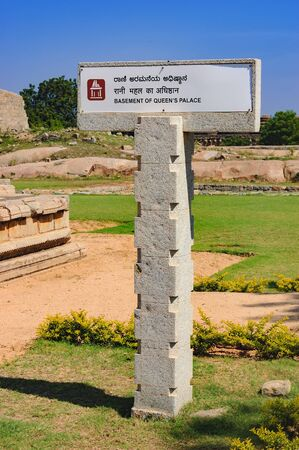 Signpost for tourists with the pointer to Basement of Queens Palace in Hampi, Karnataka, India. Stock Photo