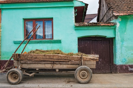An old hay cart is standing at the gate of a local vintage green house, Rasnov city, Brasov county, Romania. Typical Romanian street near Rasnov Fortress. Stock fotó