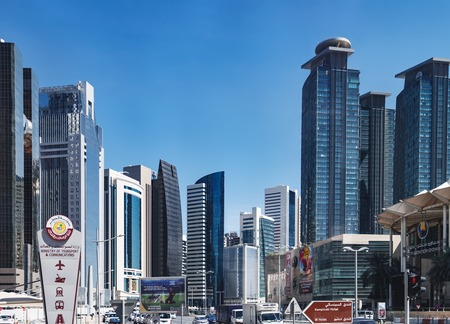 Doha, Qatar - March 3, 2018: Panoramic view of the futuristic skyline in the financial district of Qatar is seen from Conference Centre Road. Tour bus route around the Doha city