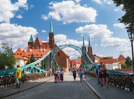 Wroclaw, Poland - August 17, 2018:Tourists visit Tumski Bridge known as the Lovers Bridge. This place is full of love locks and an important tourist attraction of Wroclaw Old Town