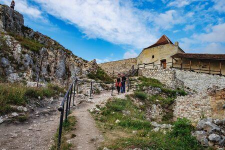 Bran, Romania - September 7, 2017: Tourists go down the rocky path and enjoy the view of the inner courtyard of the Rasnov Fortress, Rasnov city, Brasov county, Romania